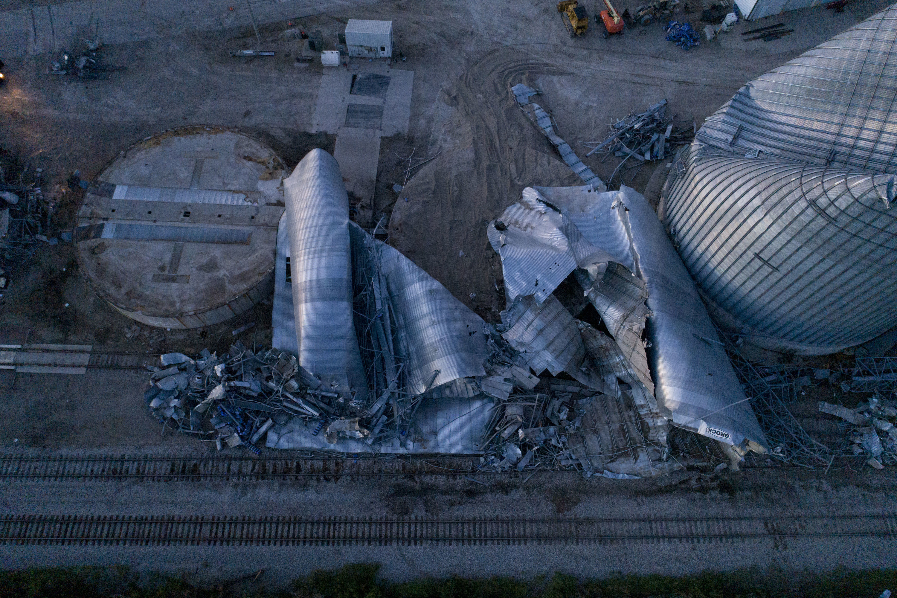 A row of mangled grain silos collapsed on the ground
