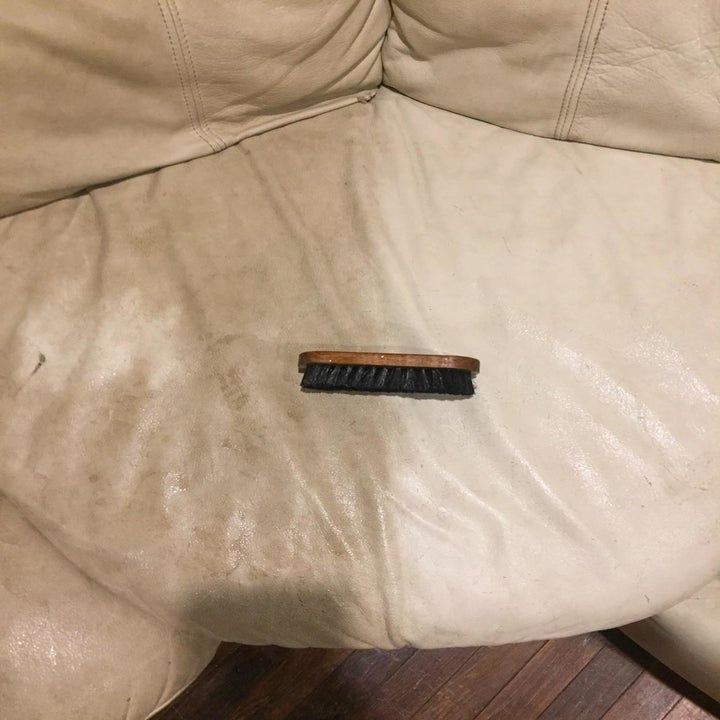 The same reviewer showing a close-up section of half the couch looking dirty and the other half looking brighter and cleaner