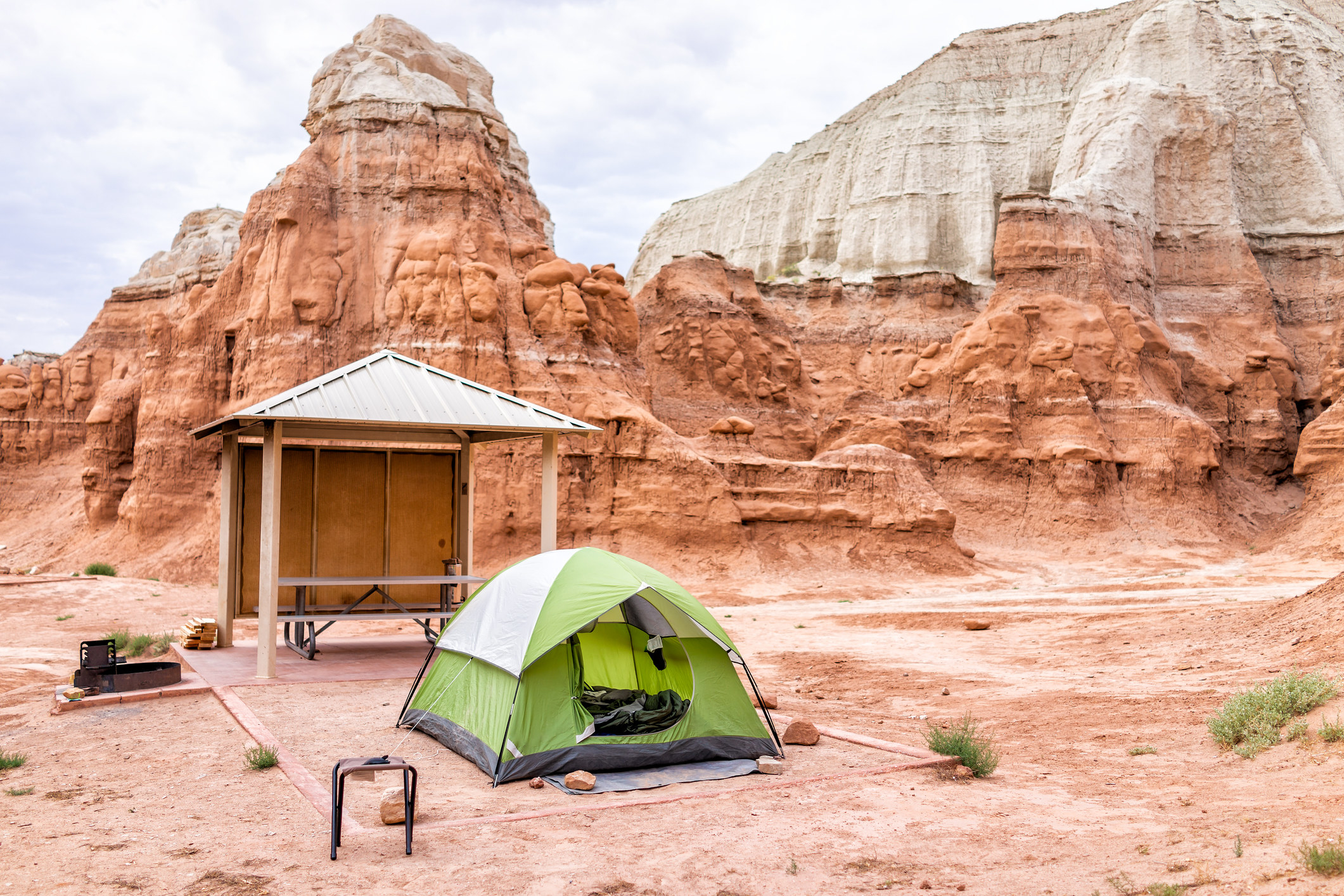 a tent in a marked camp site in Goblin Valley State Park, with white and red layers of sandstone rock formations in the background