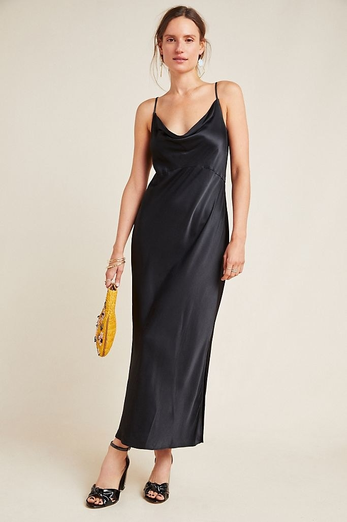 A model wearing the slip dress with heels. It has spaghetti straps, a romantic drop neckline, and a seam below the bust that create an hourglass silhouette.