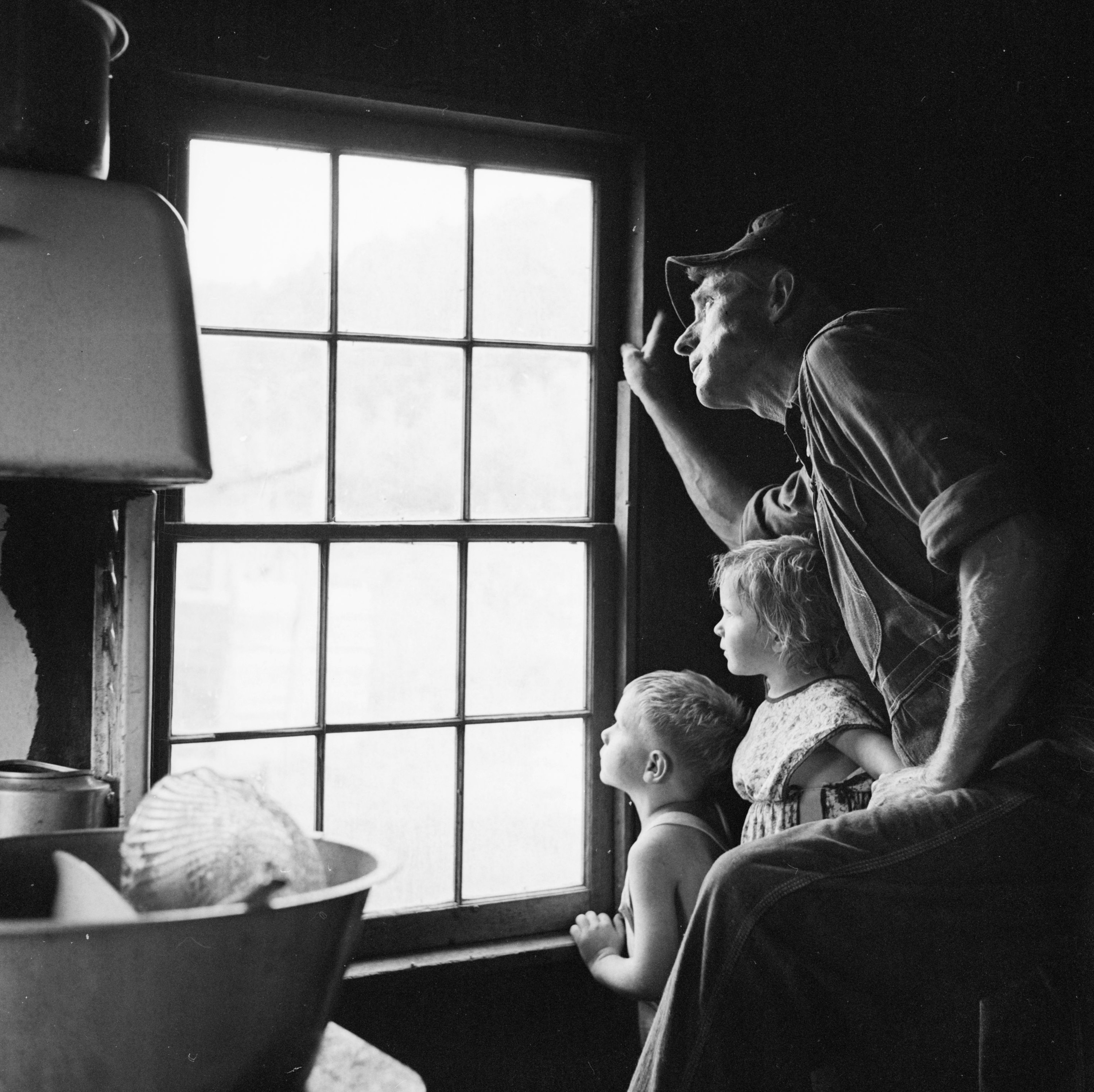 A man looks out a window with two small children