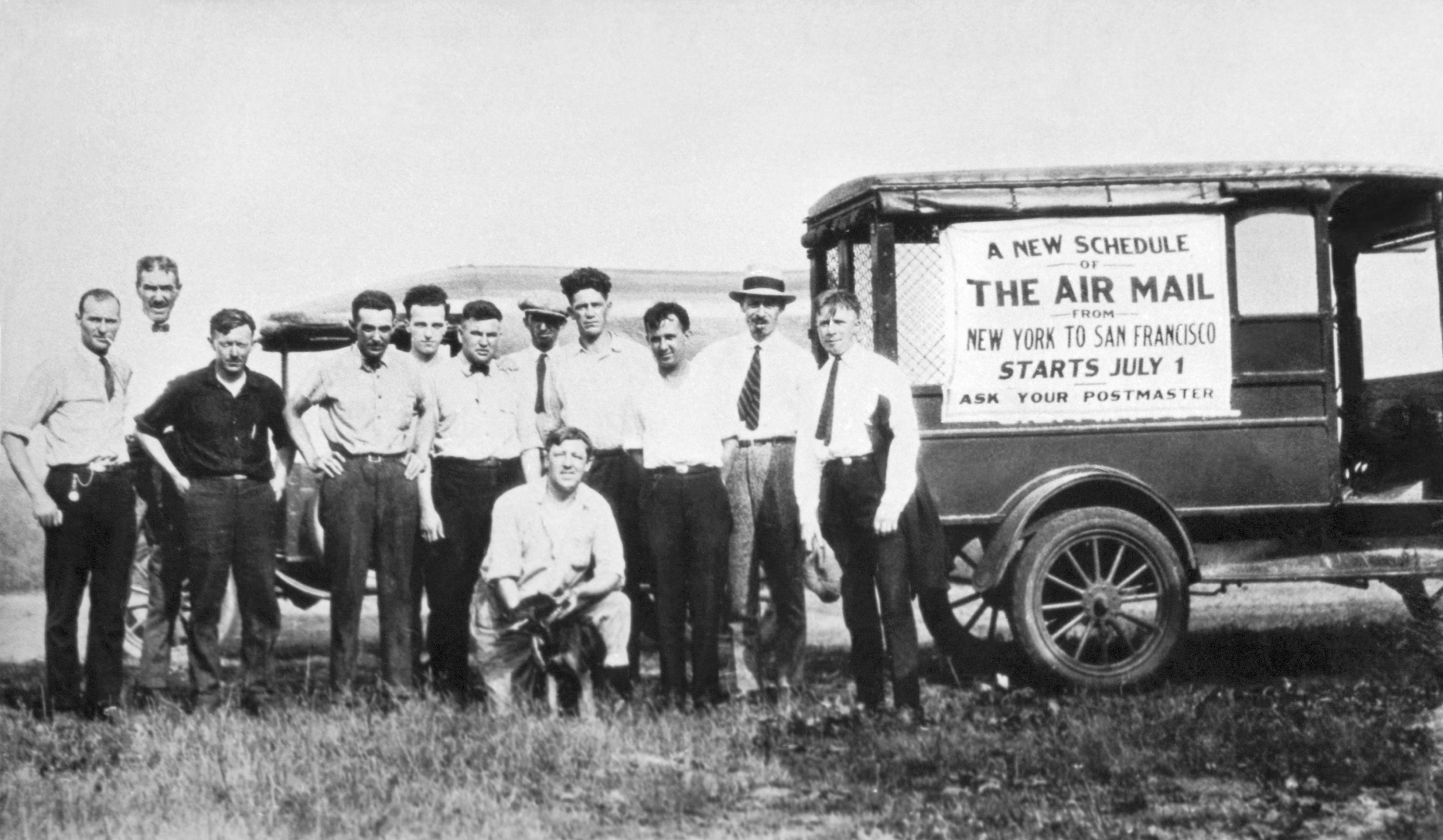 a group of white men in front of a wagon that says US Air Mail