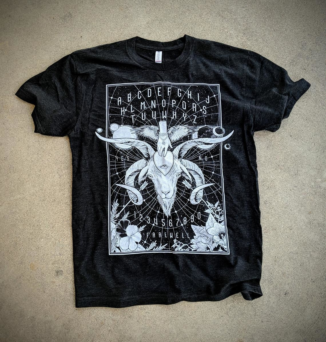 A black graphic tee with a mythical looking ram's head, floral details in each corner, an astrological starry background, a third-eye planchette, and the traditional letters, numbers, and verbiage from a spirit board