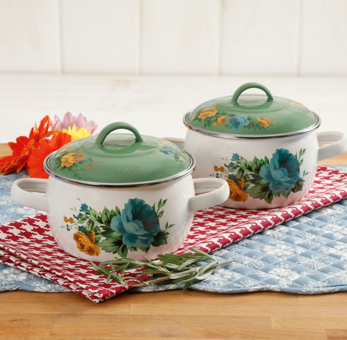 Two Pioneer Woman white and green mini Dutch ovens sitting on a red and white hound's tooth table cloth
