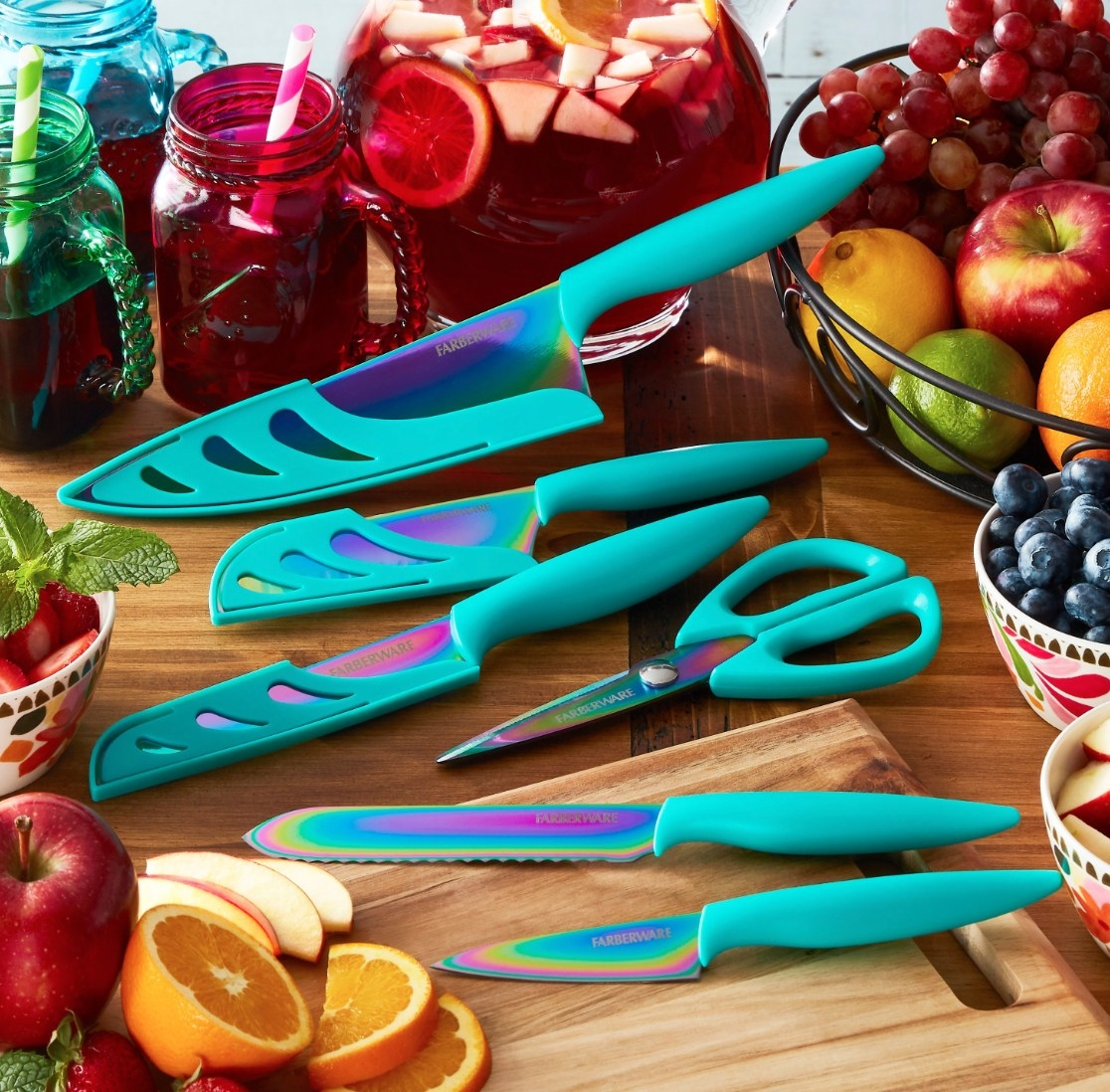Colorful titanium knives with teal handles sitting on a cutting board