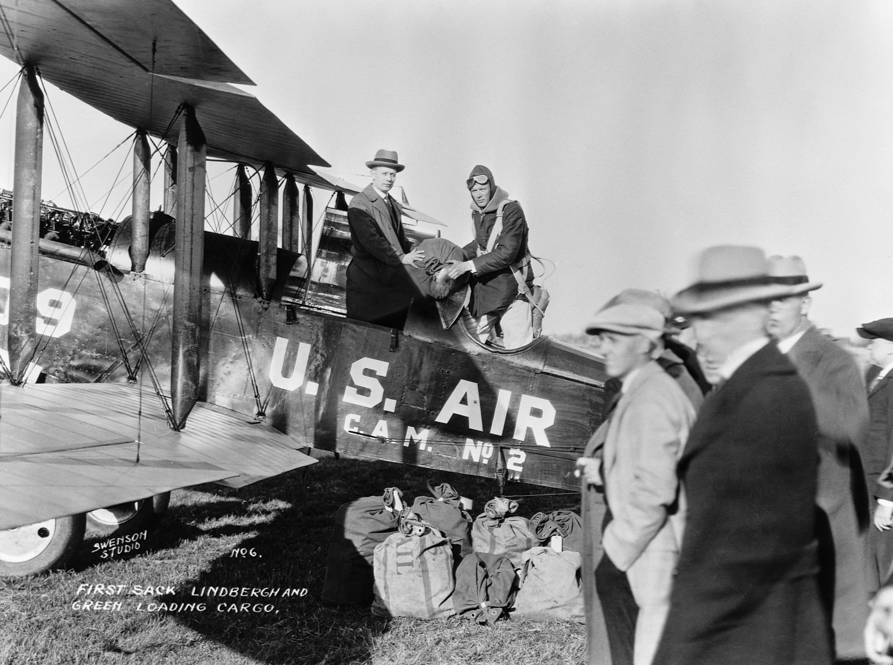 Two men, one in a fedora and one in a soft aviator helmet, stand holding a bag of mail in the cockpit of an old plane that says US Air