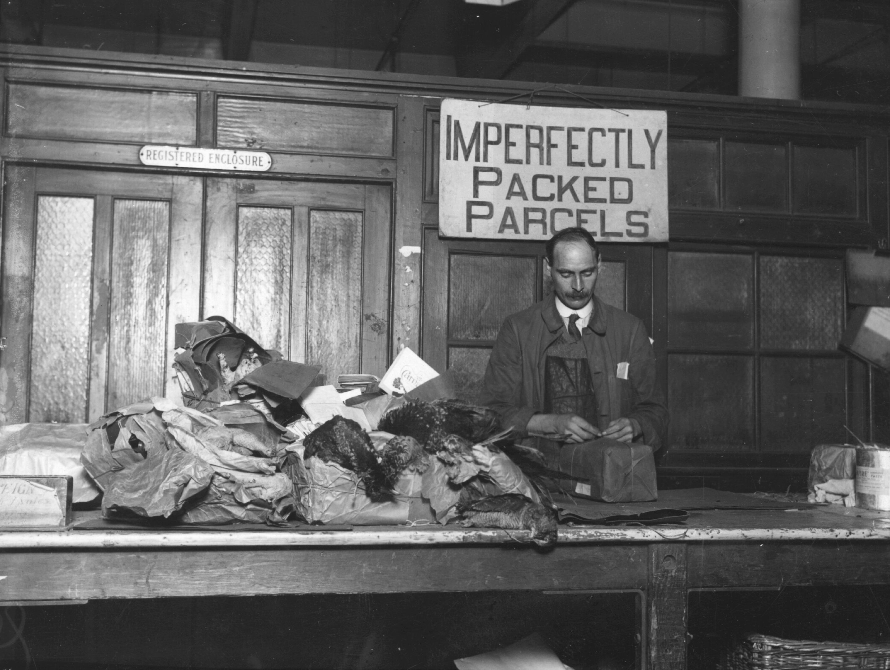 "A man in front of a pile of messy packages stands under a sign reading ""imperfectly packed parcels"""