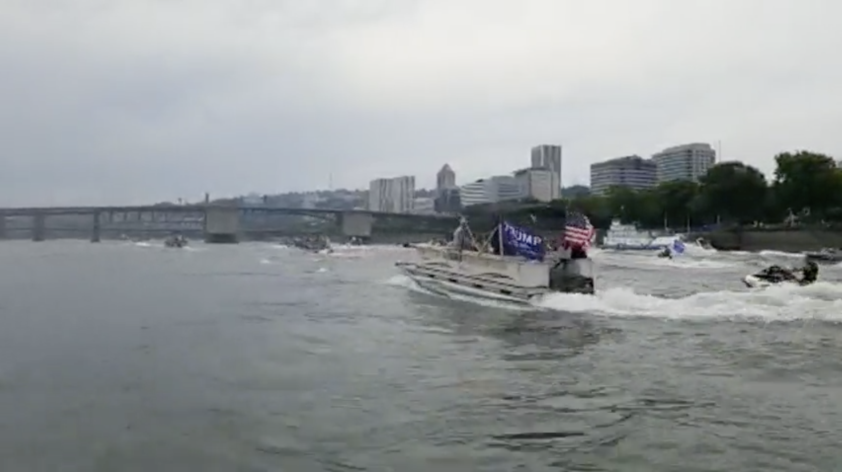 A screenshot of a video shows boats with Trump and American flags creating a wake on the Willamette River