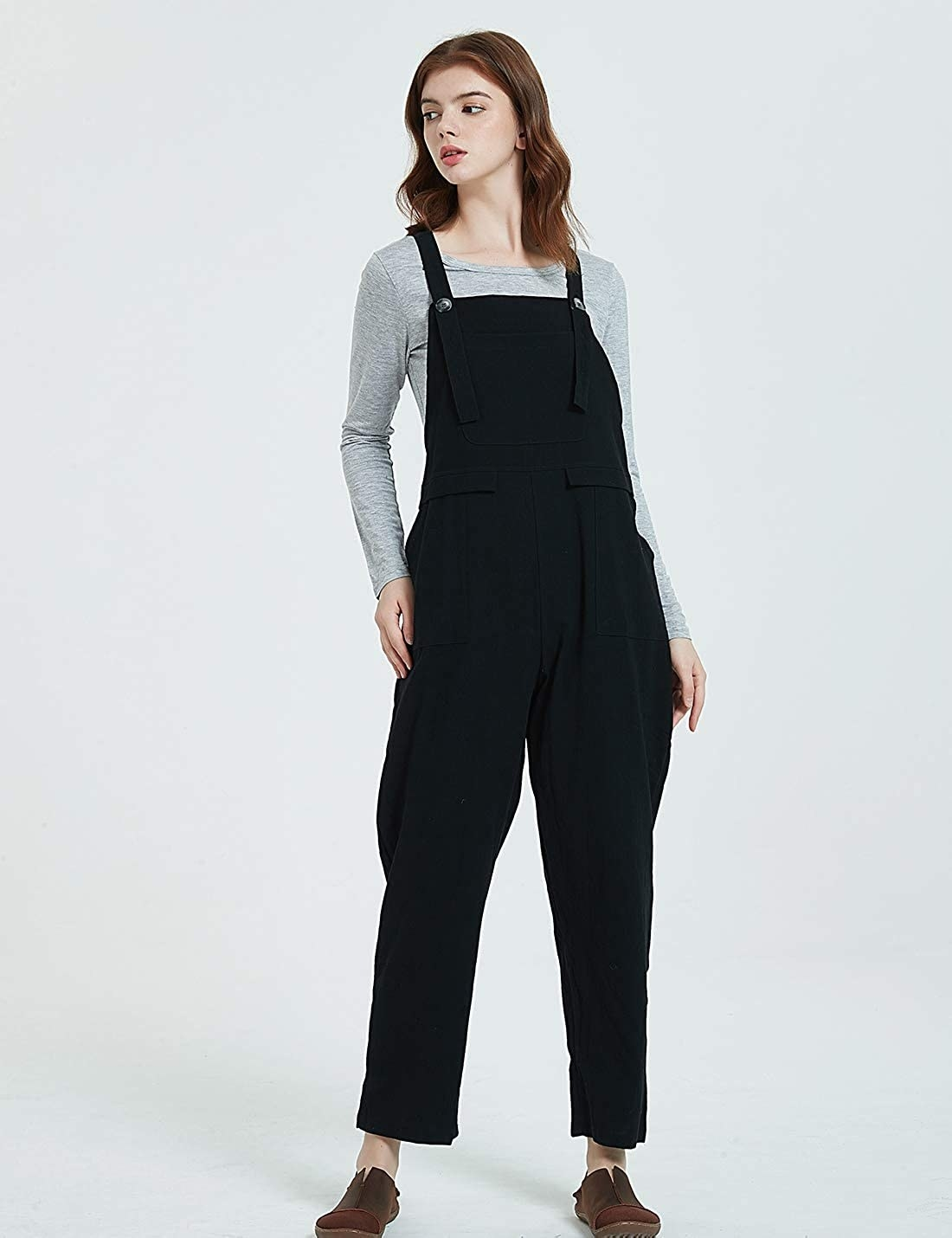 A person wearing the button-up overalls with a shirt underneath. The overalls have front pockets and hit the ankle.
