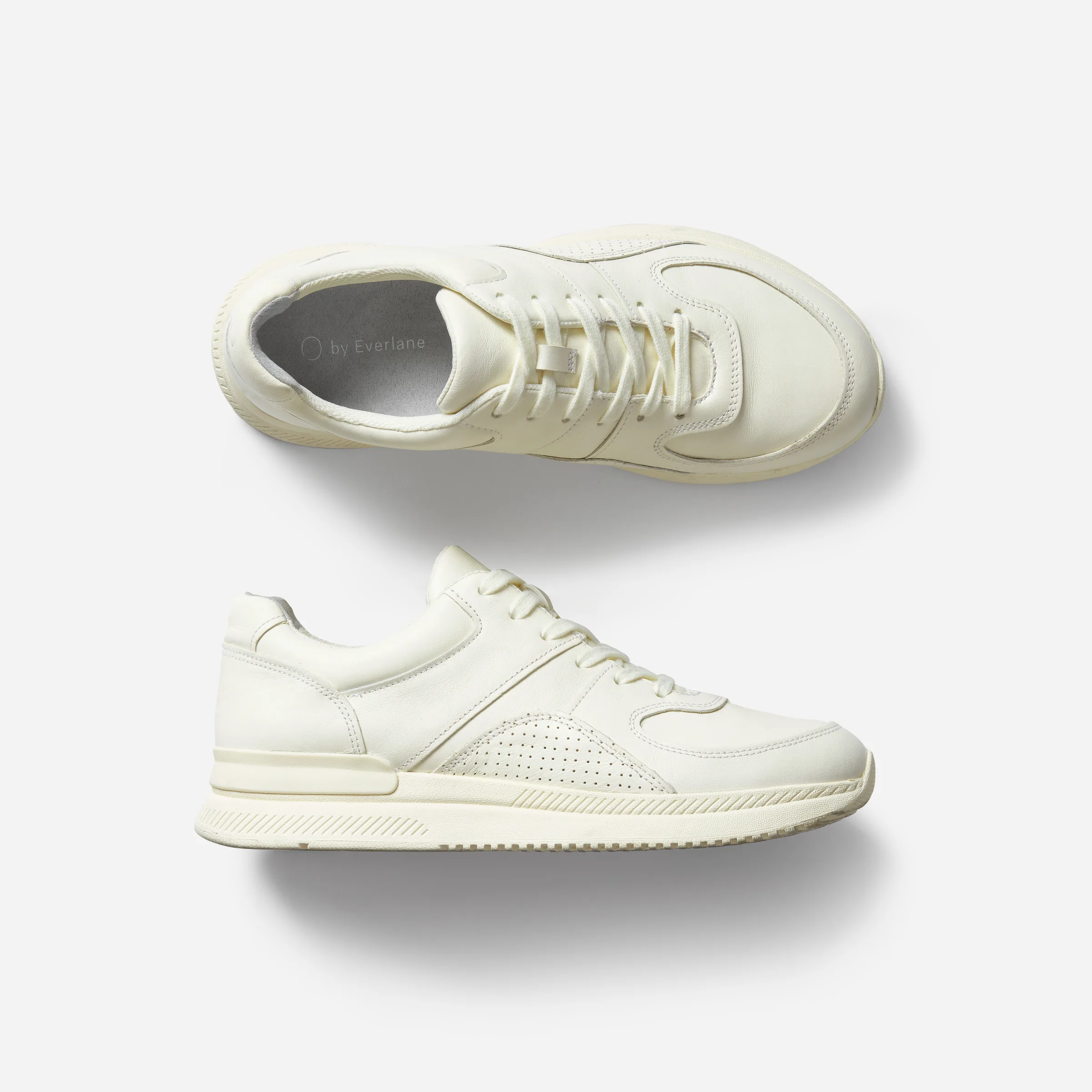 A side and top-down view of a white lowcut sneaker
