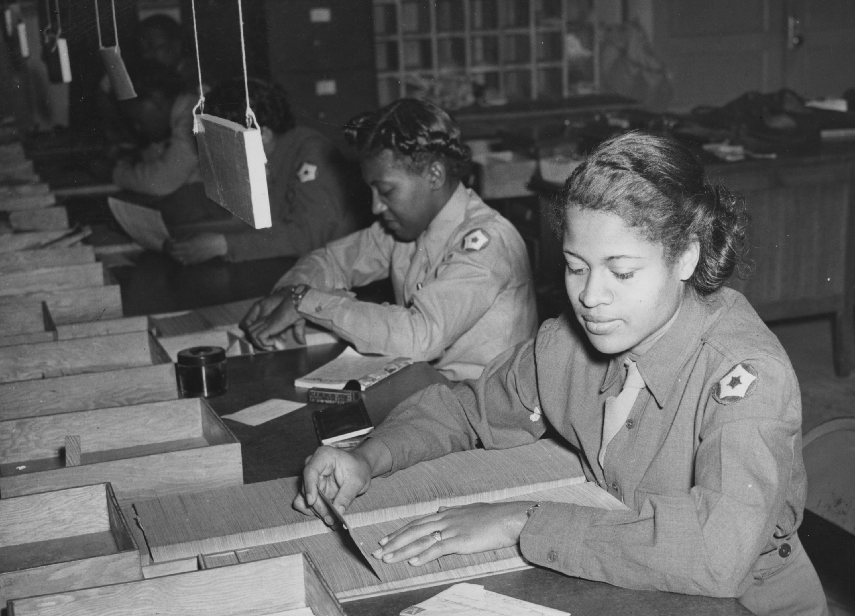 Two black women in military uniforms sort mail