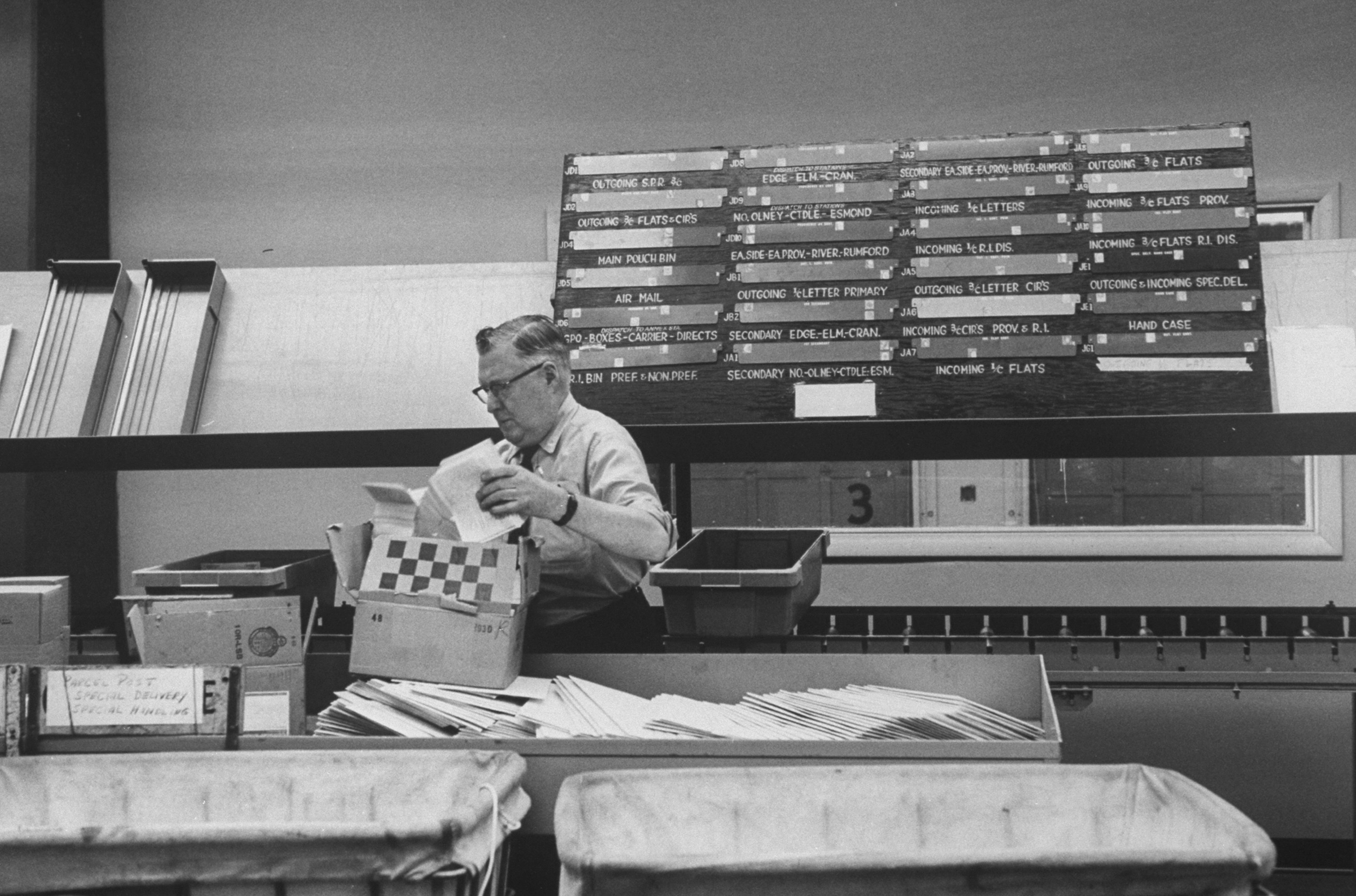 A middle-aged white man in glasses unloads mail onto a conveyer belt