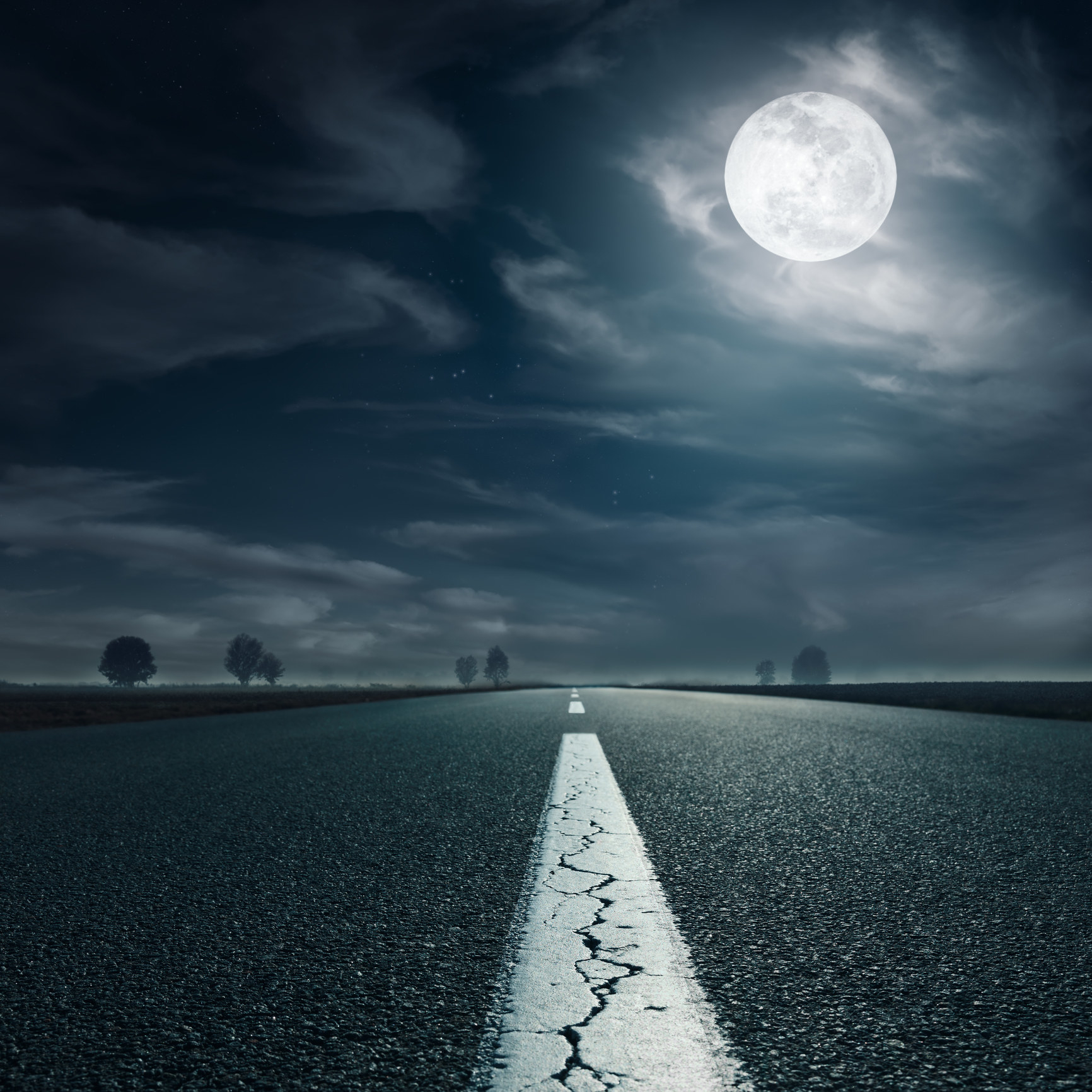 An eerie, empty road at night with a full moon in the sky