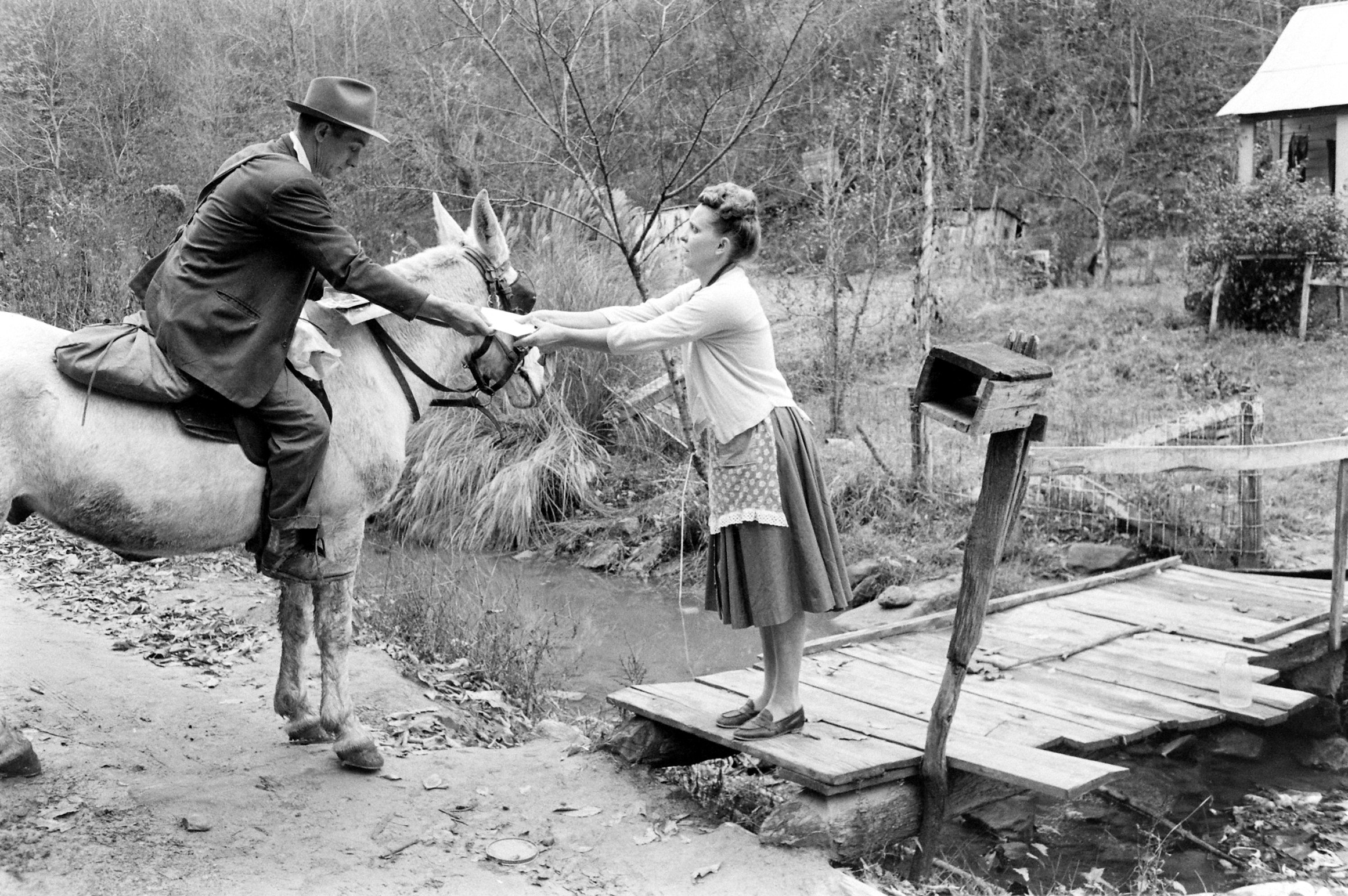 A man on horseback hands a letter to a woman in a dress and apron standing on a wooden bridge