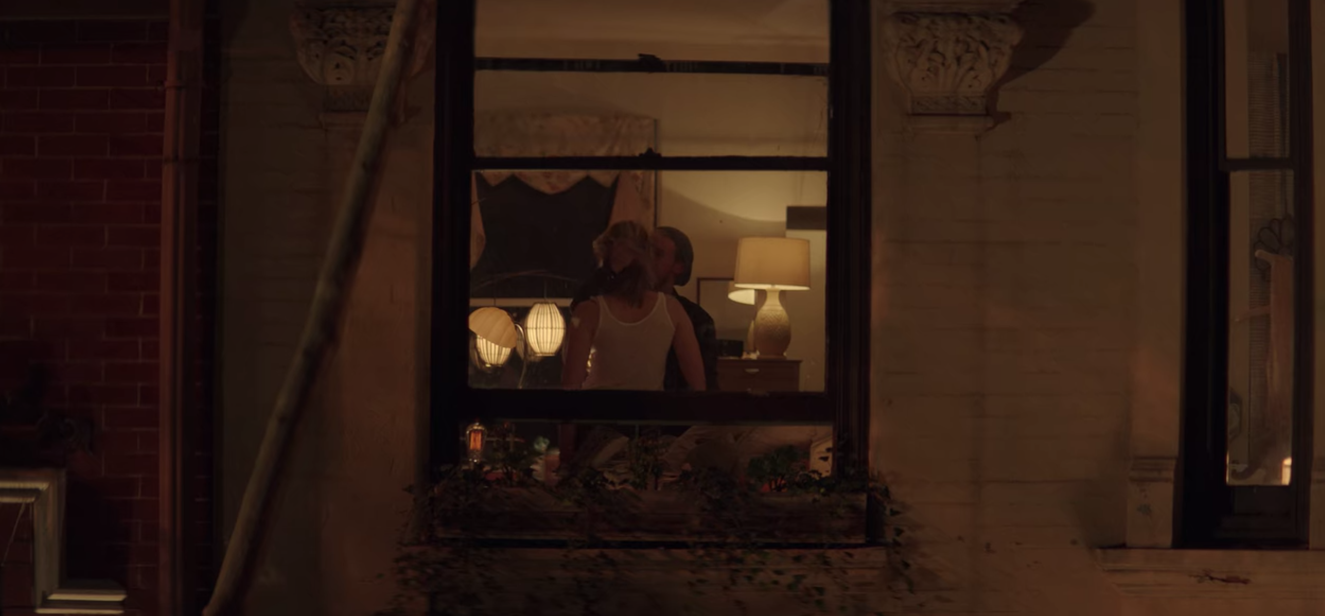 A man and woman are seen getting intimate from outside of a window