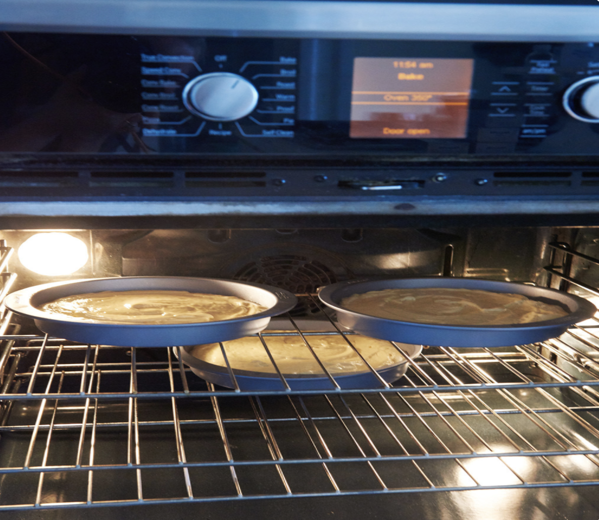 An oven with its door open, while three cakes are baking inside