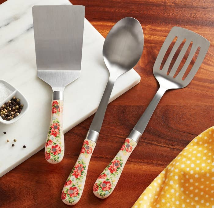A silver spatula, spoon, and slotted spatula all with vintage floral handles