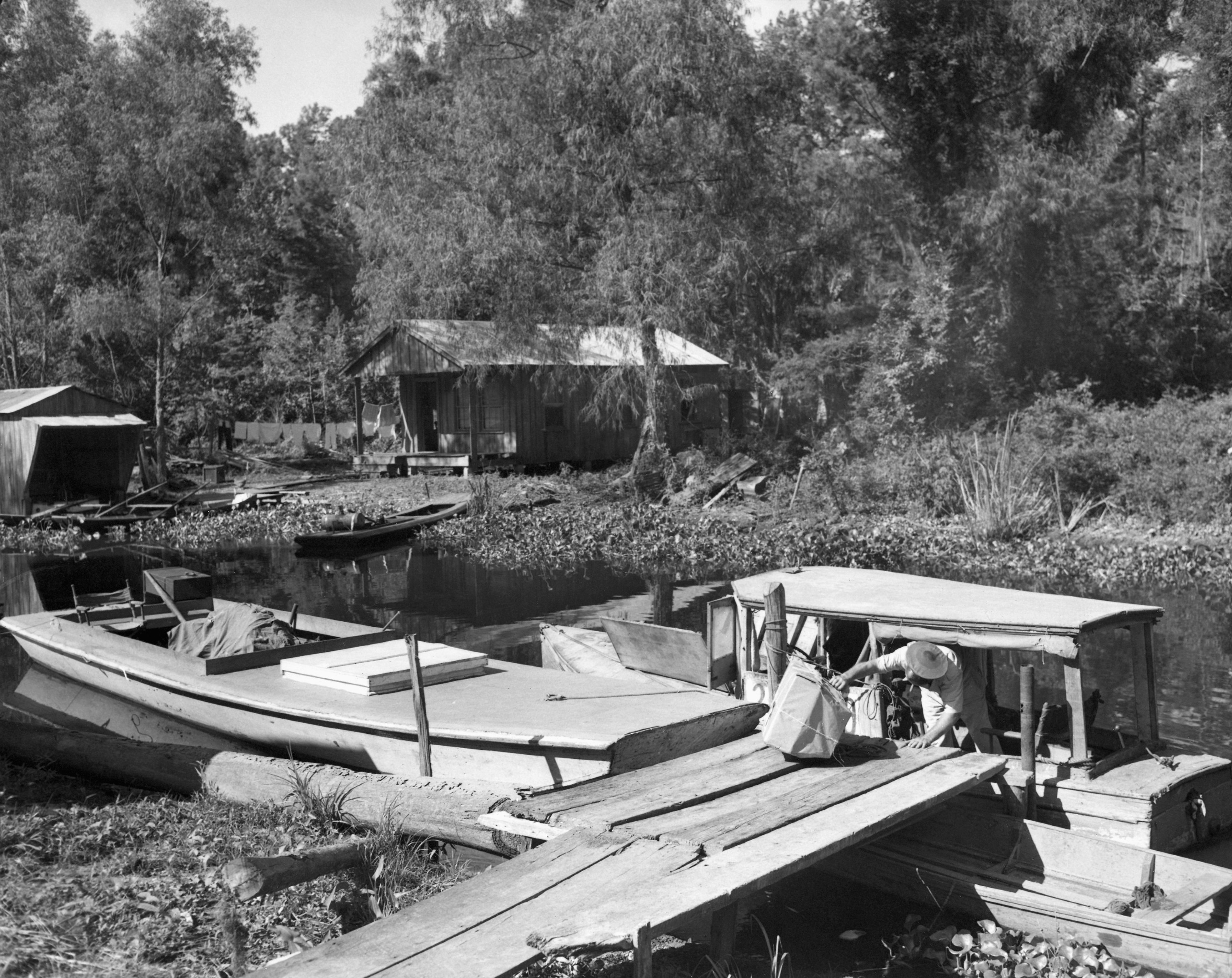 A man gets on a wood boat with a sack of mail in a bayou