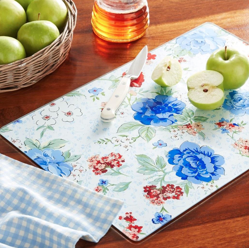Floral-print glass cutting board sitting on dark-grain wood table