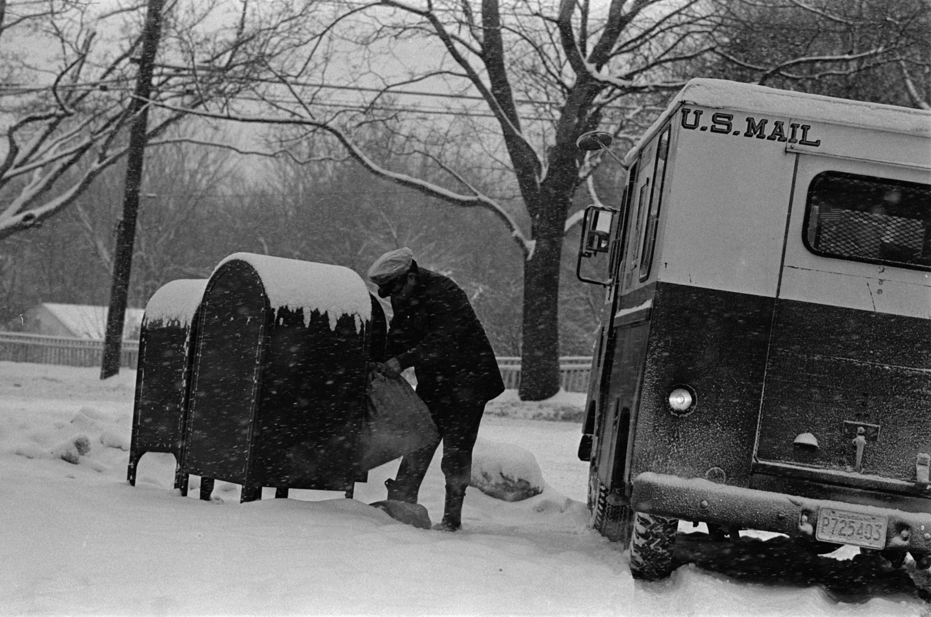 A man unloads mail from mailboxes covered by snow
