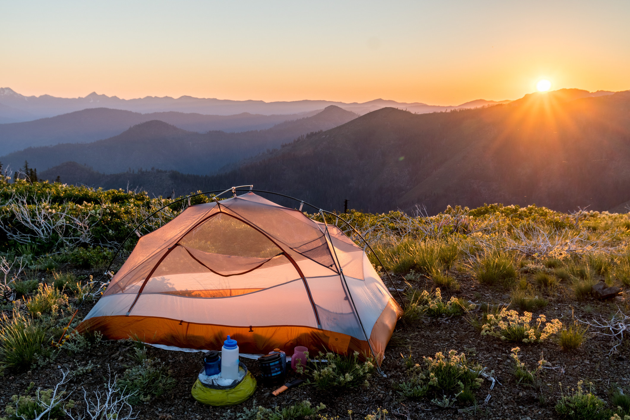 a remote tent on a flat mountain top with the sunset in the background