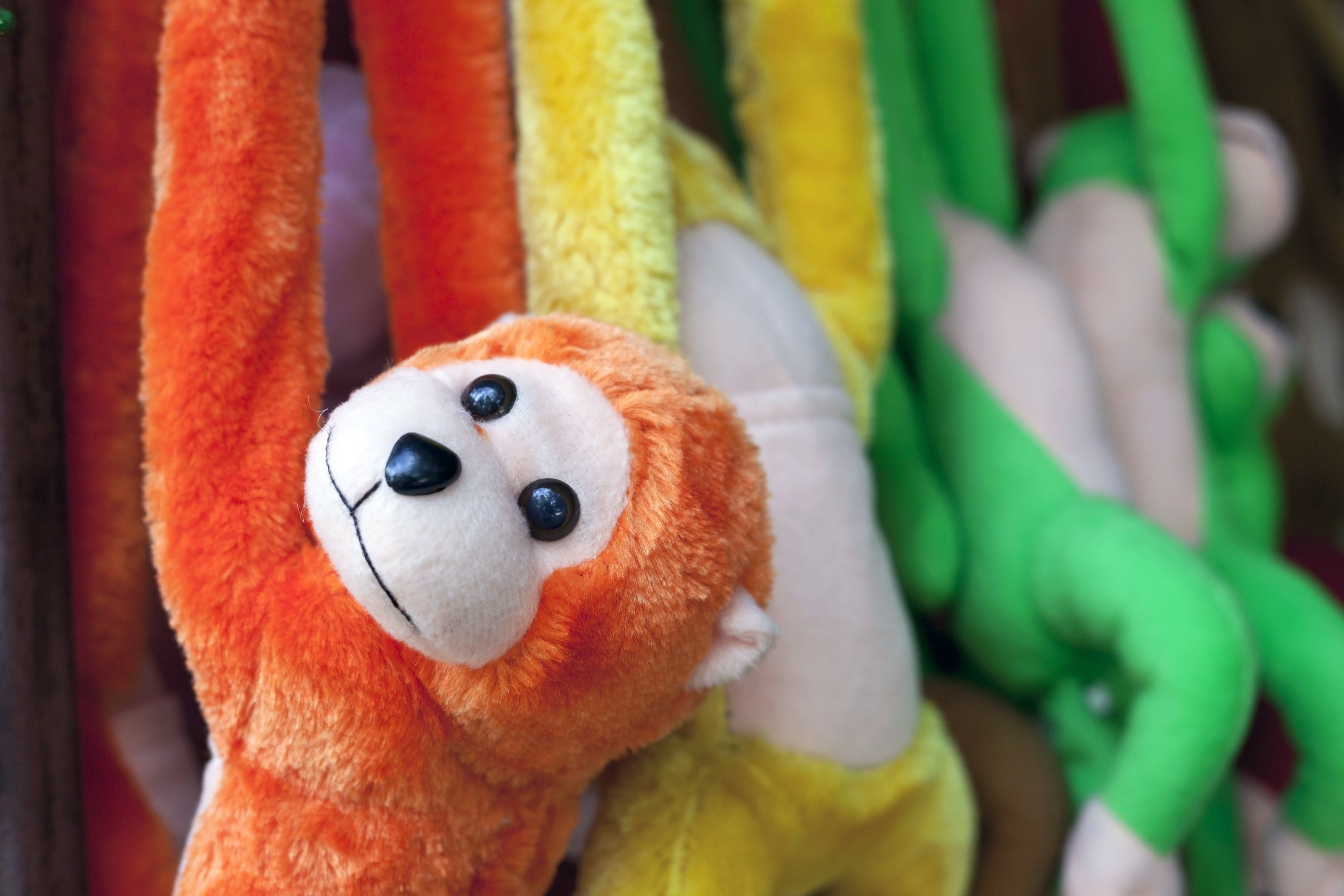 A stuffed orange monkey doll hanging by its arms
