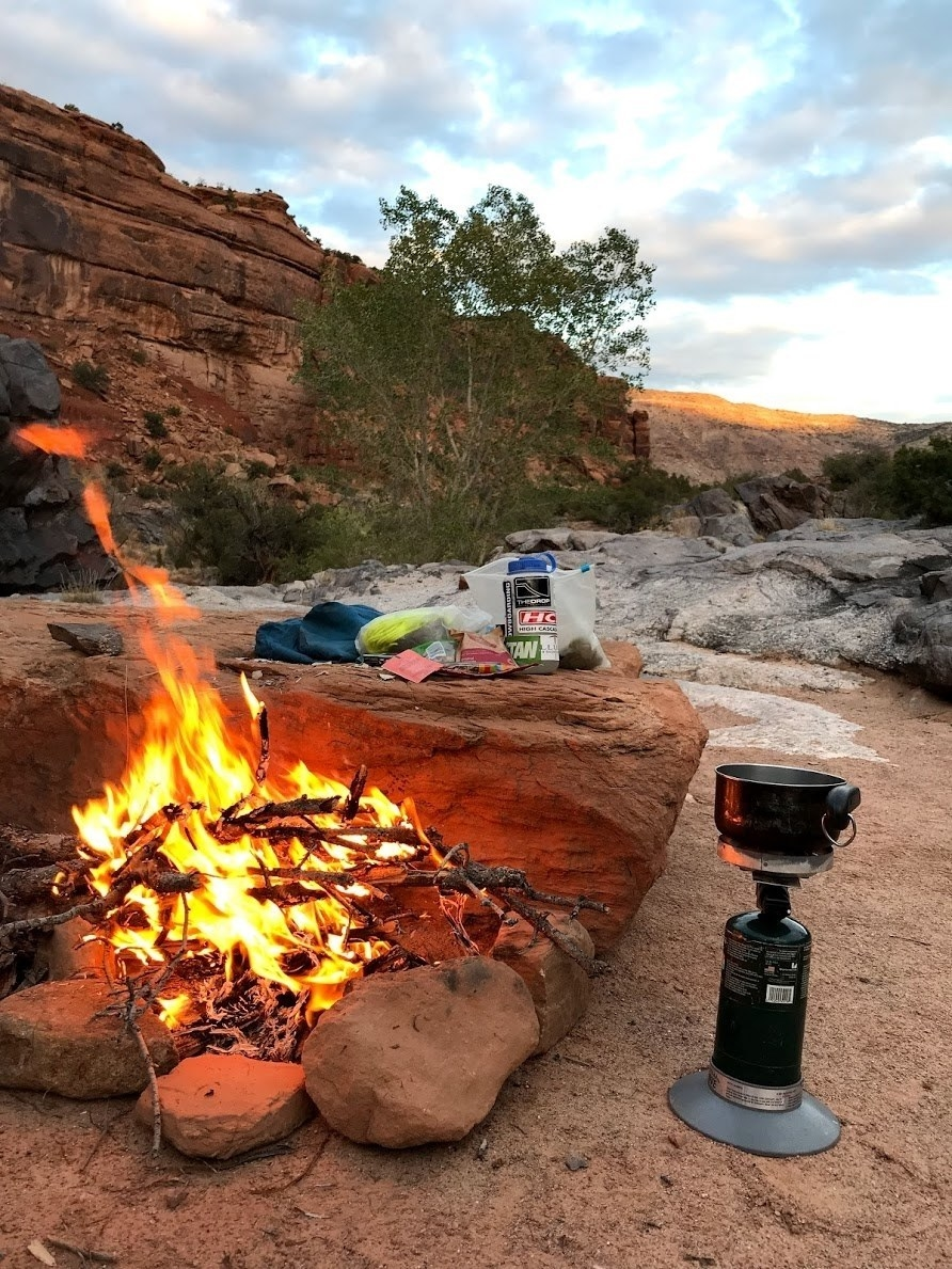 roaring campfire surrounded by rocks and camping gear