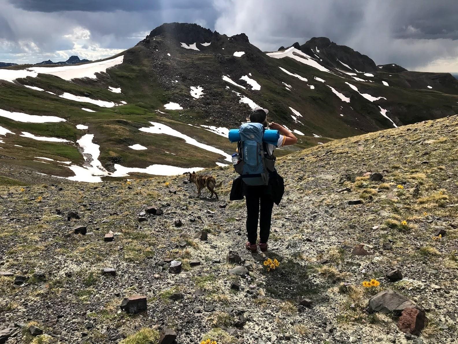 woman wearing a big backpack walking across rocky mountain terrain