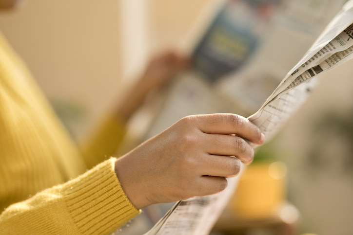 A pair of hands holding a newspaper