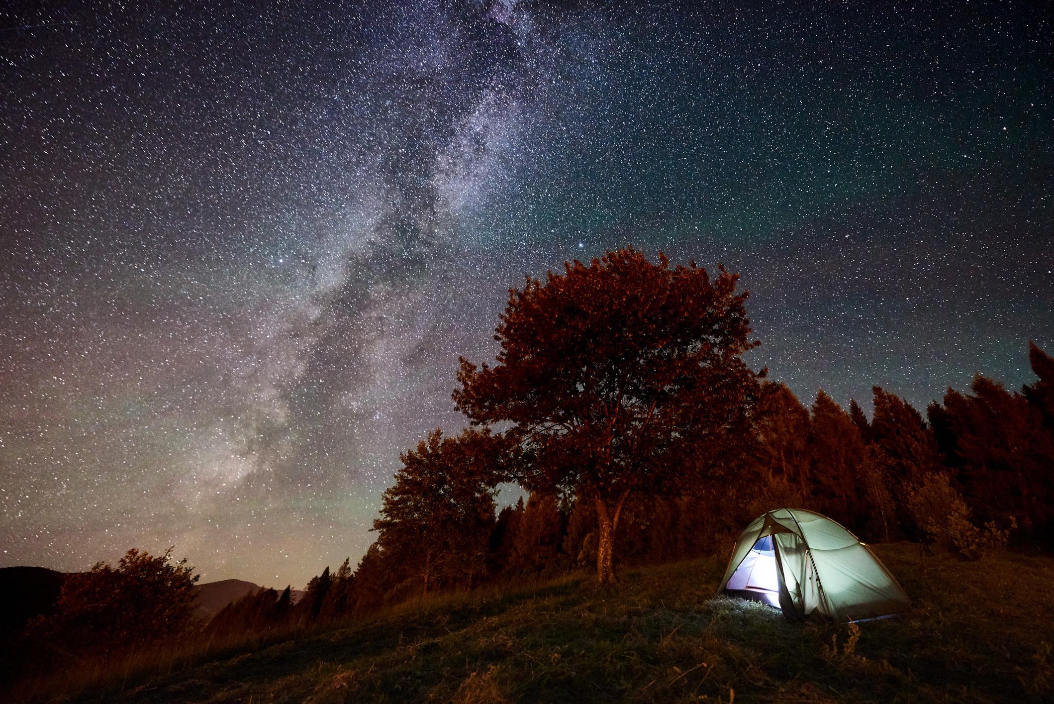 illuminated tent under starry night sky