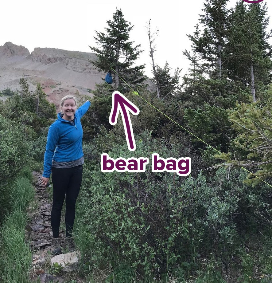 woman on a rugged path pointing towards a small bear bag hanging in the trees