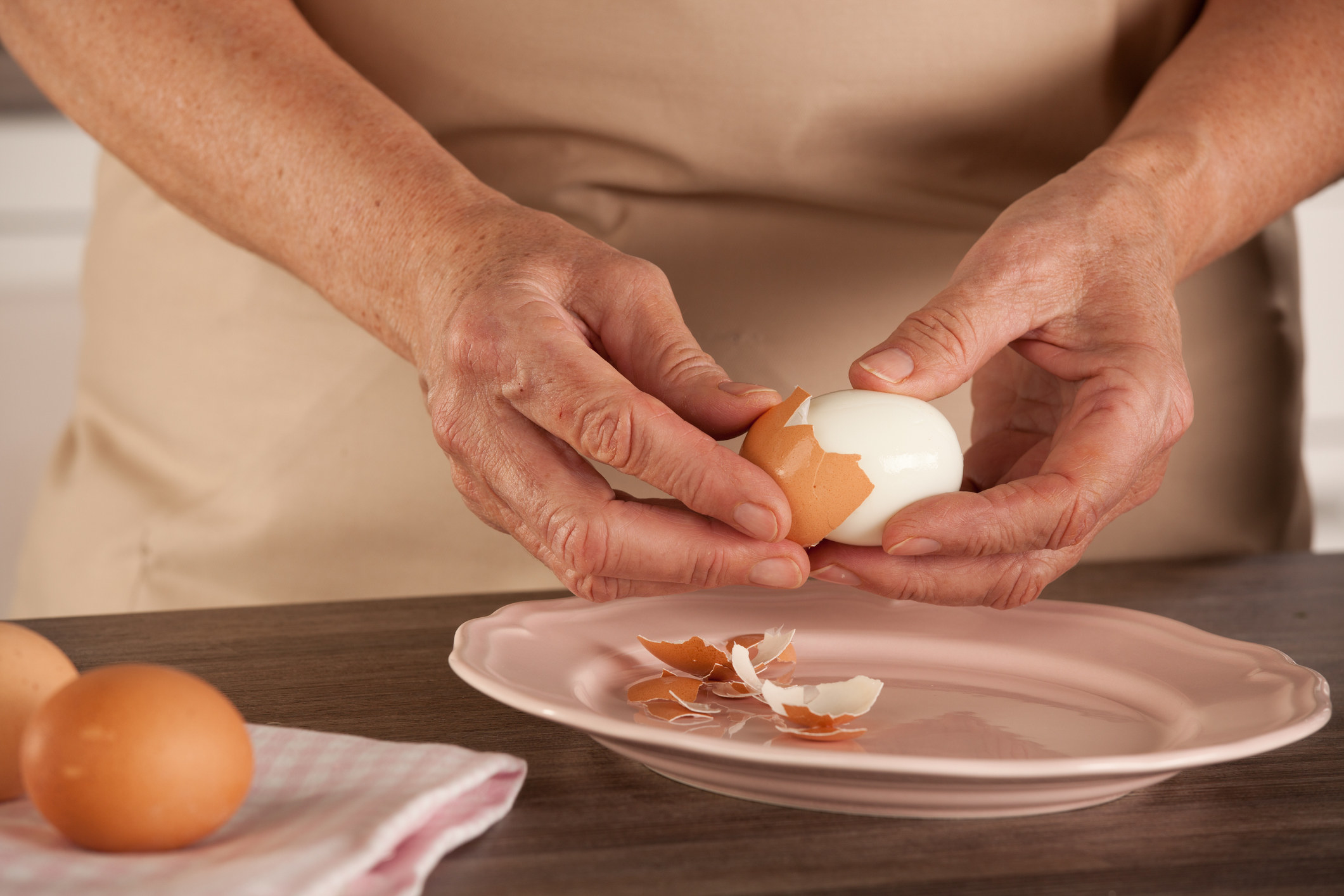 Hands peel the shell of a boiled egg