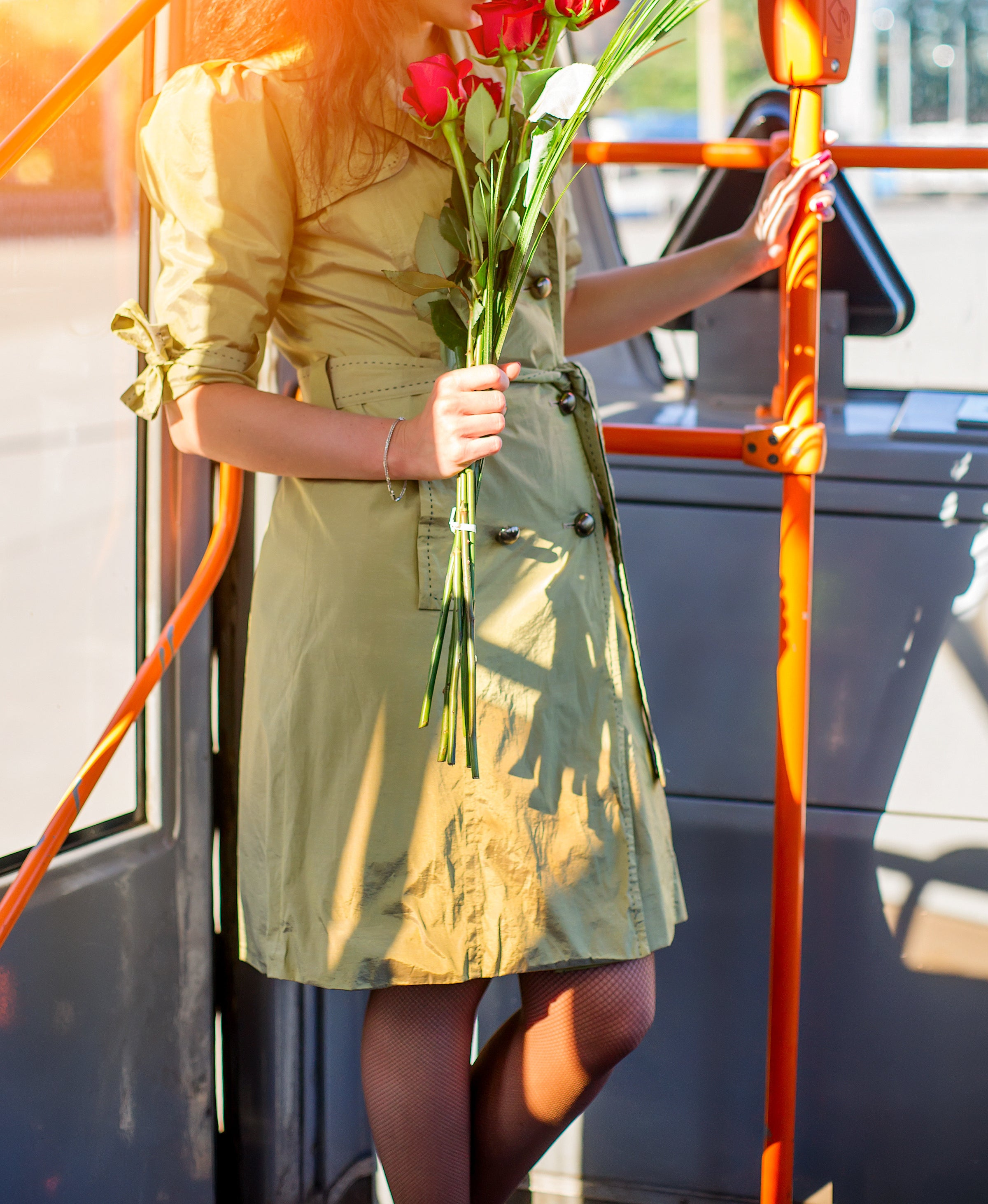 A woman on a bus holds a bunch of roses