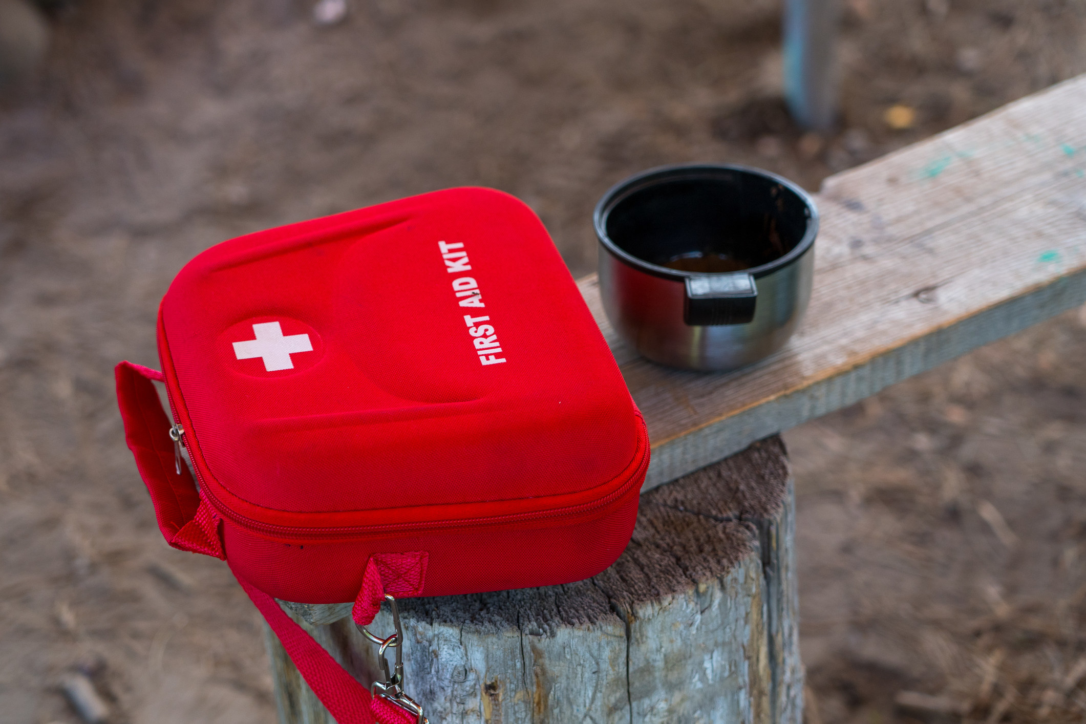 red first aid kit case on wooden bench