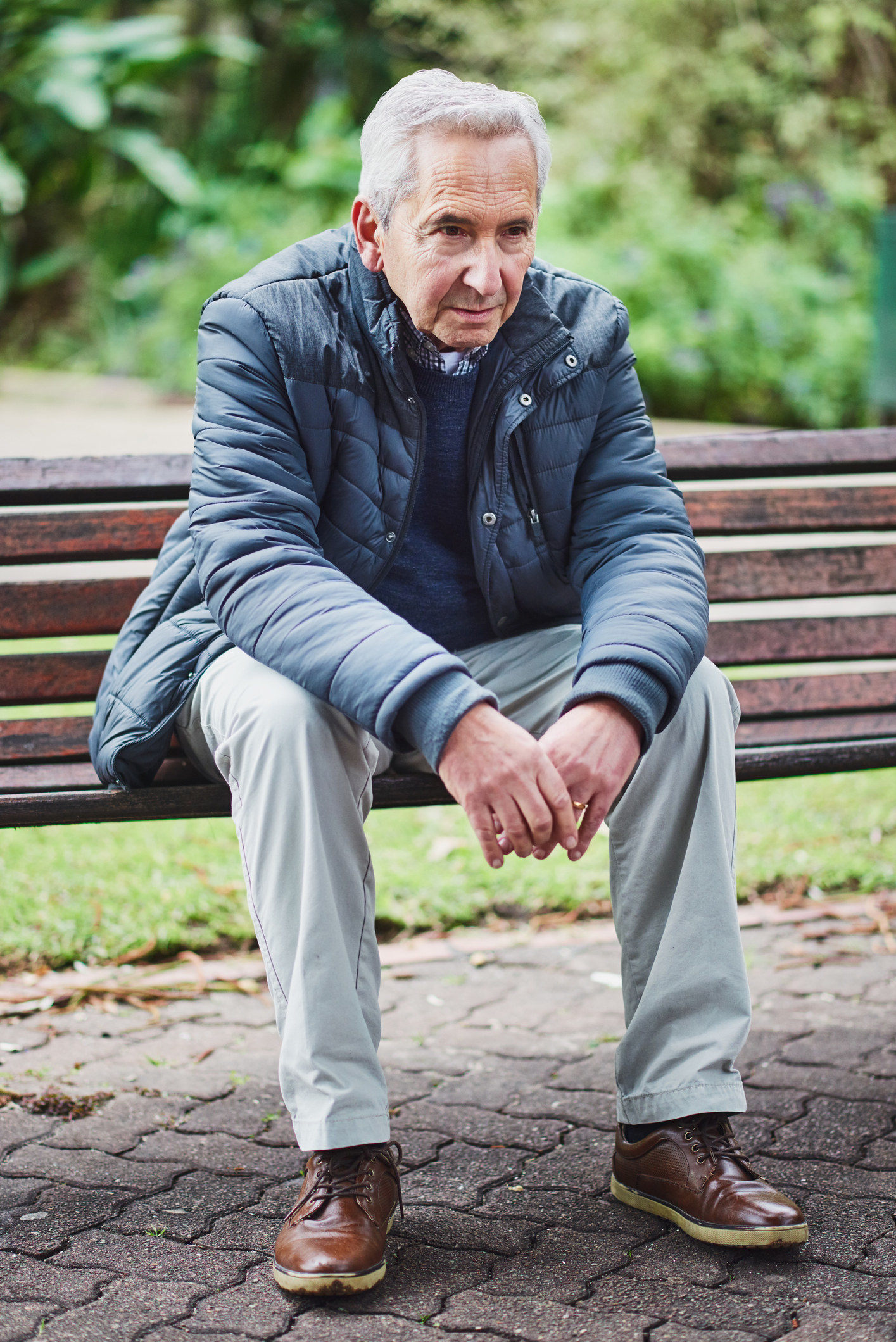 A man sits calmly on a bench