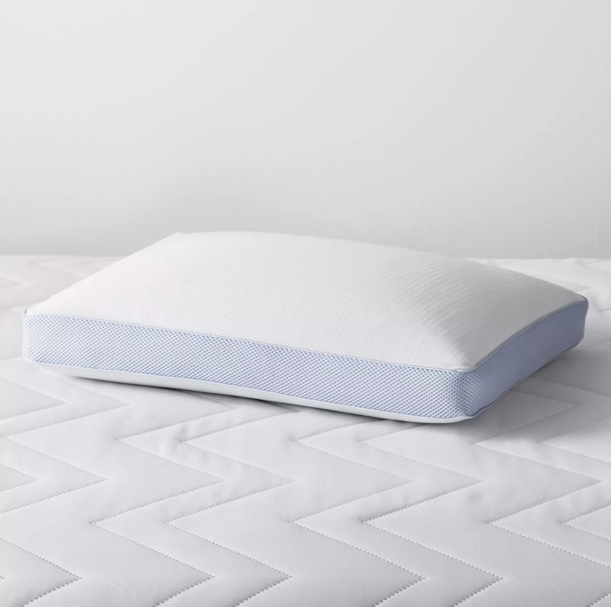 The white pillow with blue edges