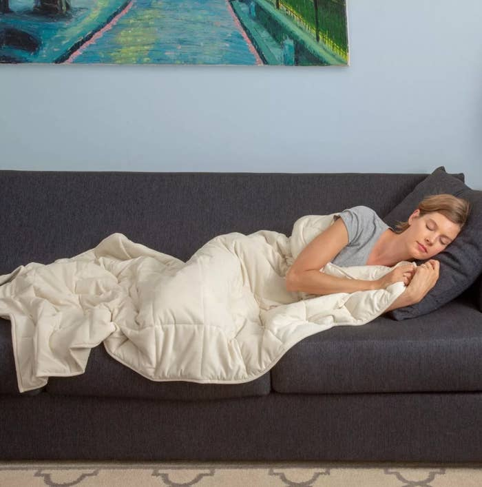 Woman cuddled up with a cream-colored weighted blanket on a gray couch