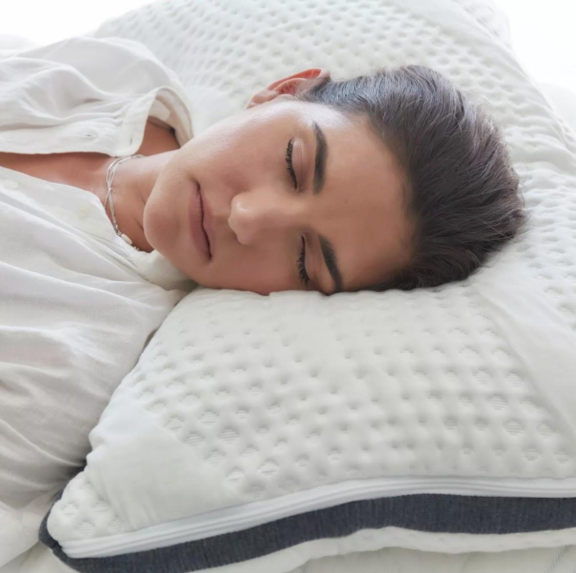 Model sleeping on the textured white memory foam pillow