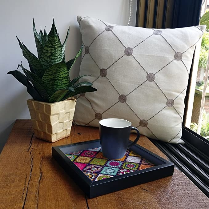 Black square tray with a colourful mandala design in the centre.