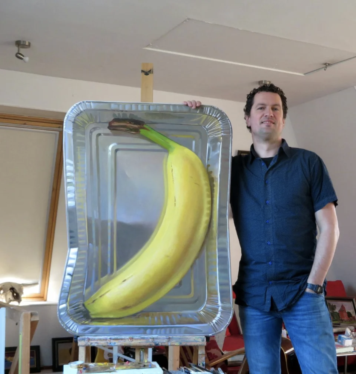A man has painted a huge banana into a pan and it looks very real