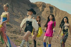 ITZY poses in the desert in sparkly dresses of multiple colors and patterns, high boots, and jewelry