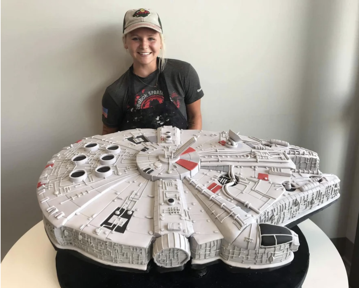 A baker stands over an epic Millennium Falcon cake