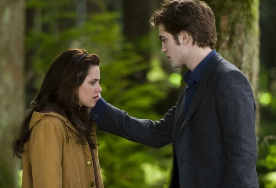 Edward caressing Bella's face while standing in a forest