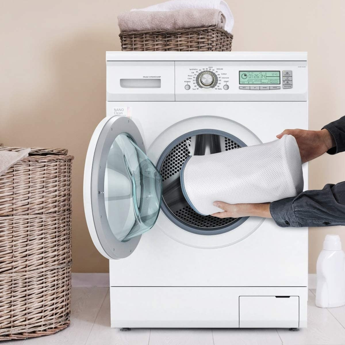 A person putting the mesh bag filled with shoes into a washing machine