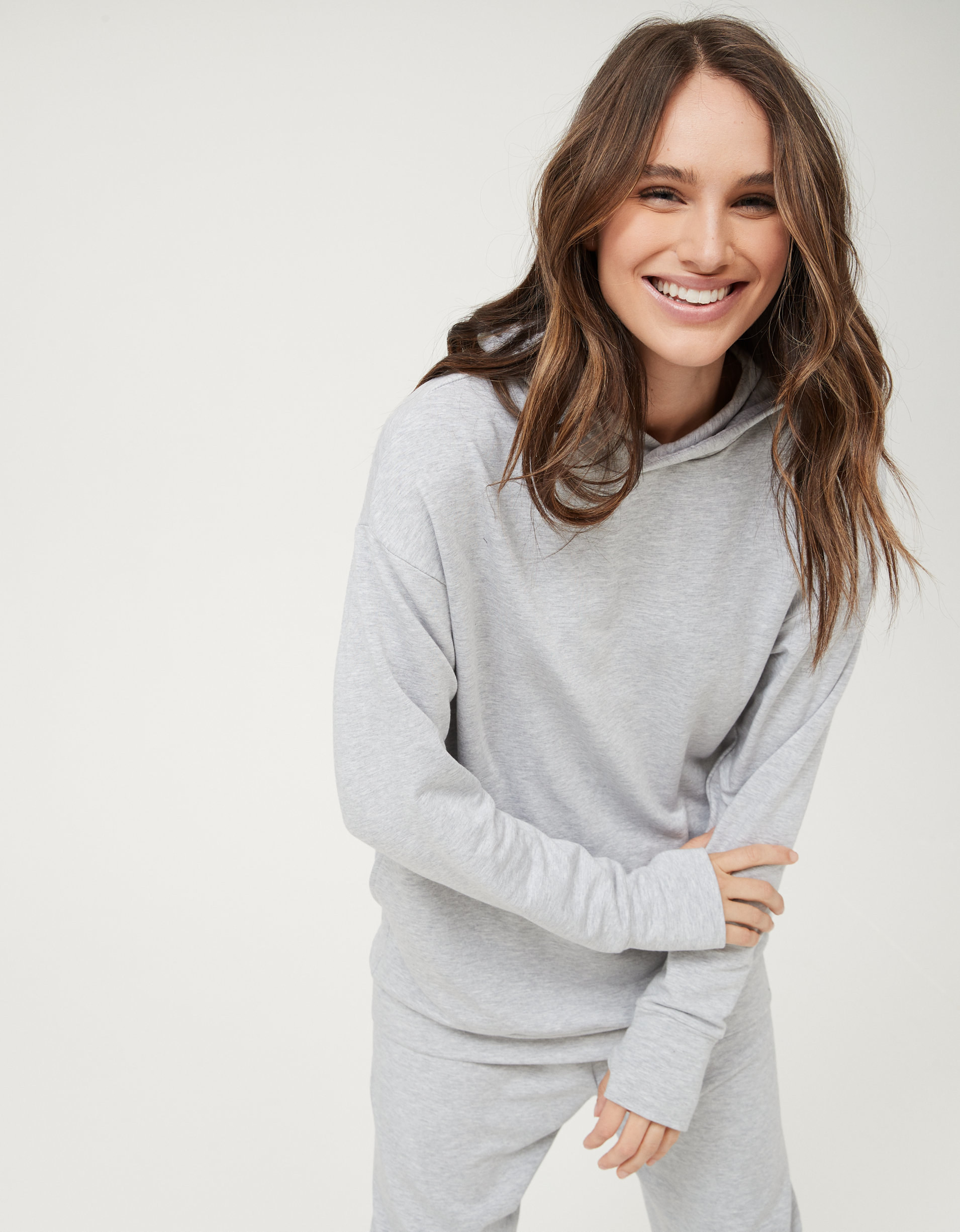 model in grey hoodie with matching sweatpants