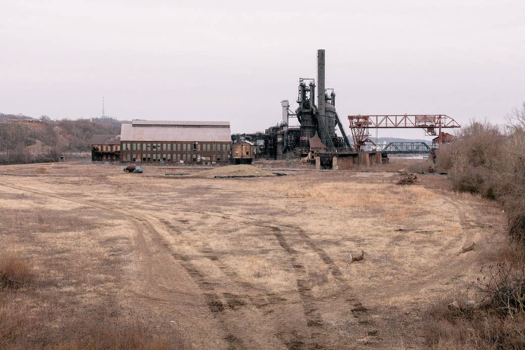 A desolate and abandoned industrial building under cloudy skies