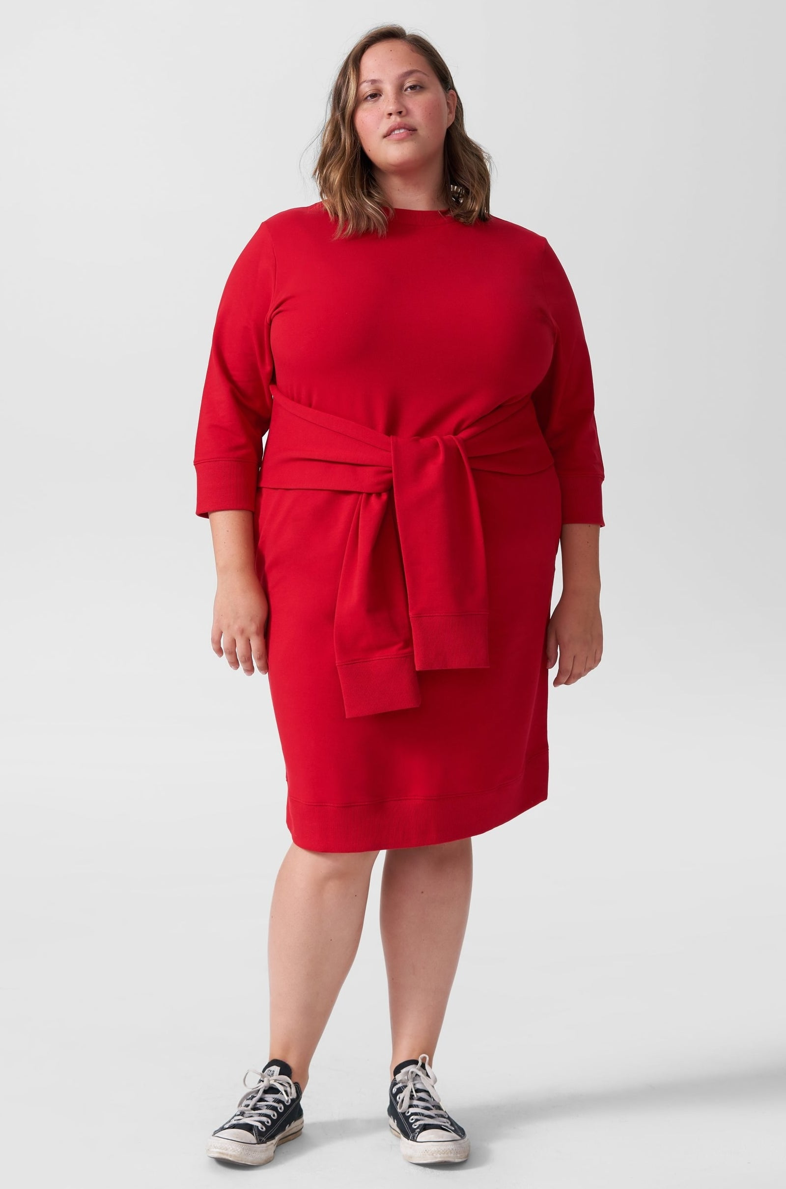 model in red knee length three quarter sleeve dress with additional sleeve-style ties that knot around the waist
