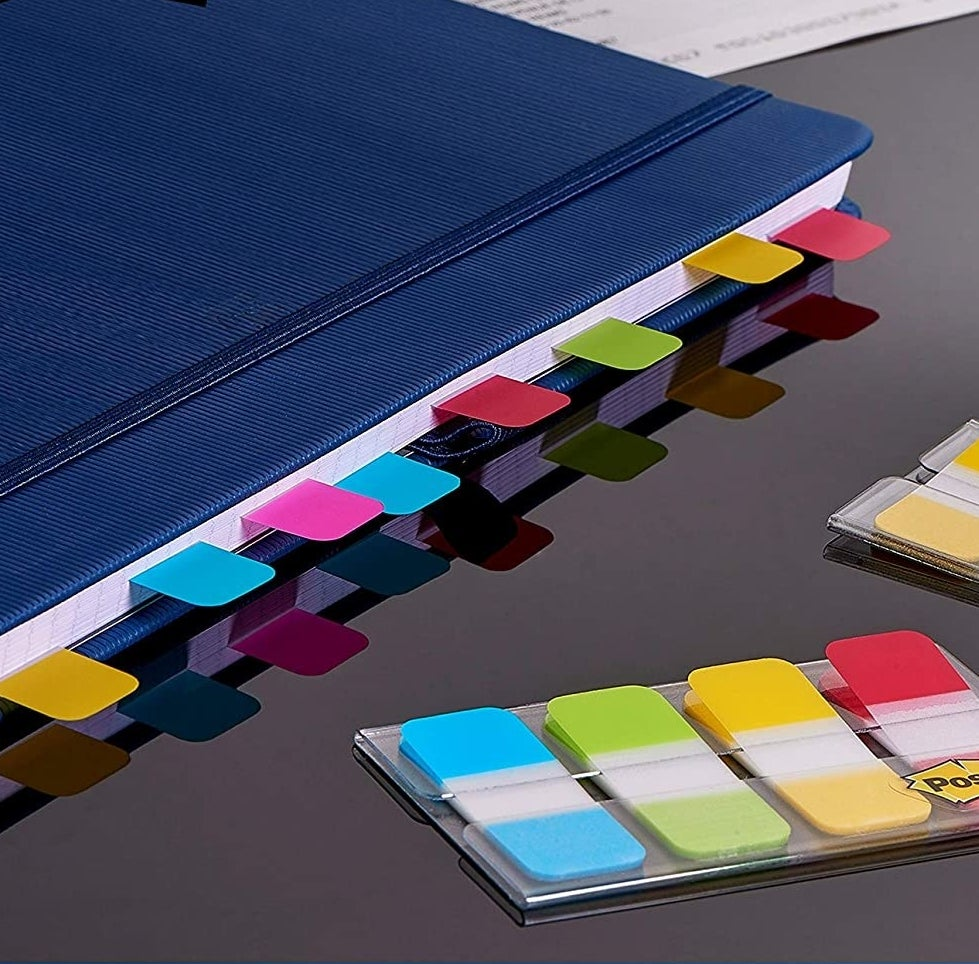 A pack of Post-It flags next to a notebook filled with Post-It flags