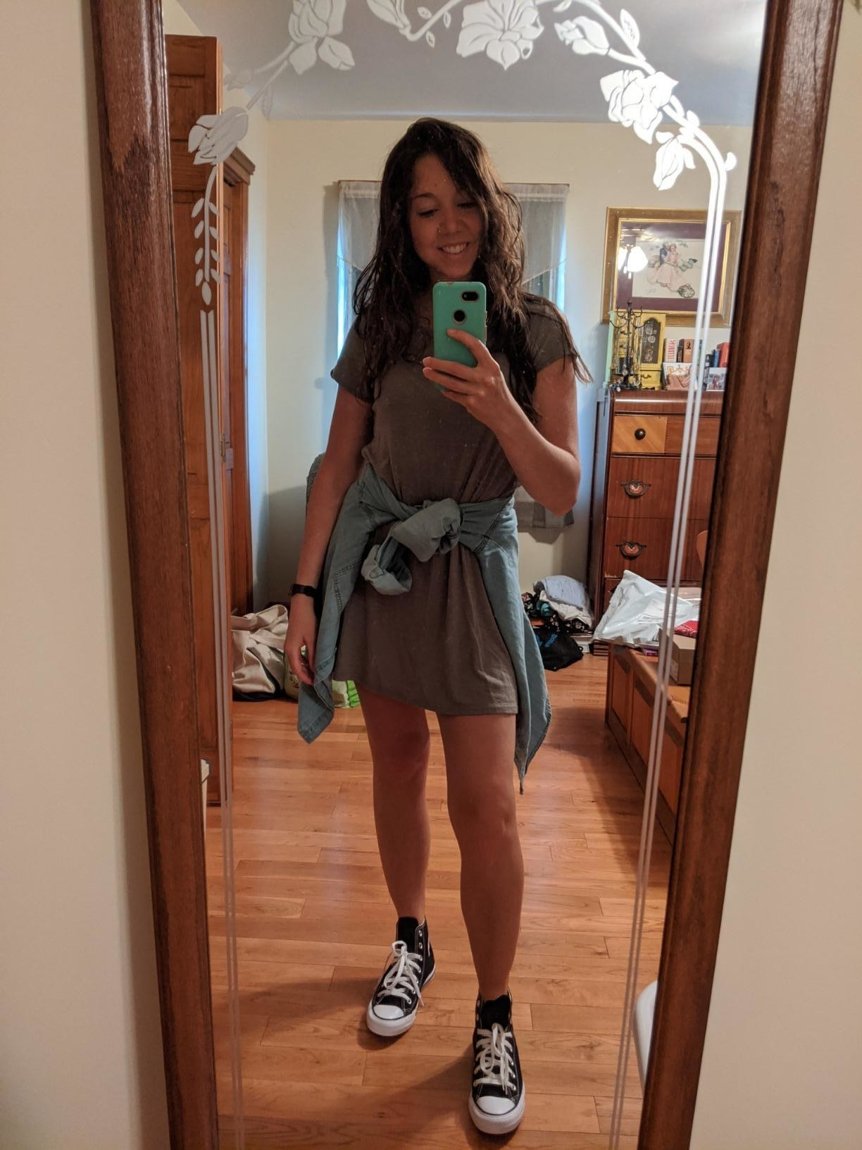 Reviewer wearing black Converse with a gray T-shirt dress