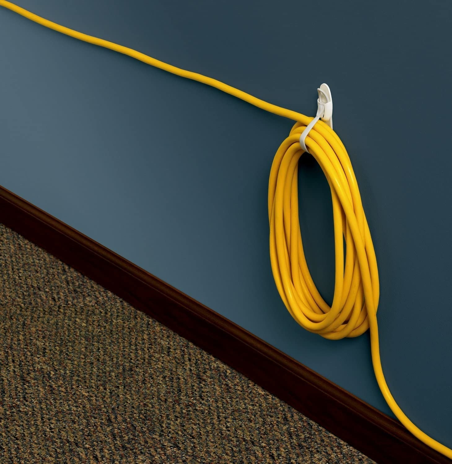 The cord bundler stuck to a wall with a cord wrapped around it